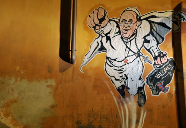 "A view of a street art mural by Italian street artist Maupal which depicts Pope Francis as a superman, flying through the air with his white papal cloak billowing out behind him and holding a bag bearing the word ""Values"", in downtown Rome near the Vatican on January 28, 2014. The image, created by Italian street artist Maupal, was tweeted today by the Vatican communication twitter account ( @PCCS_VA ). Flying forward with his fist raised, the heroic pontiff -- crucifix swinging in the wind -- carries his trademark black bag, with the word ""values"" written across it in white. AFP PHOTO / TIZIANA FABI"